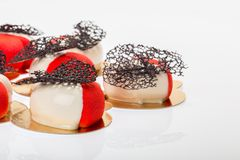 Group of french mousse cakes in form of heart, covered with red and white glaze. Modern European dessert with chocolate veil decoration stock photo