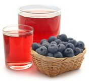 Group of fresh blueberries with juice. In a glass over white background Royalty Free Stock Photos