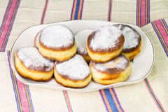Group of fresh donuts sprinkled with powdered sugar in plate on old ukrainian linen tablecloth Royalty Free Stock Image