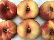 Group of fresh doughnut peaches fruits. On a white marble plate Royalty Free Stock Image