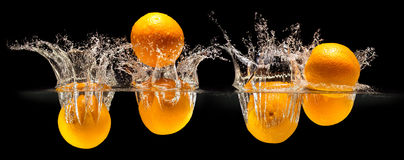 Group of fresh fruits falling in water with splash on black background Stock Image