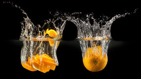Group of fresh fruits falling in water with splash on black background Stock Photography