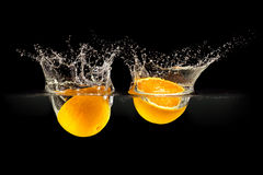 Group of fresh fruits falling in water with splash on black background Royalty Free Stock Photo