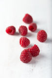 Group of fresh, organic raspberries over a wooden background Royalty Free Stock Photo