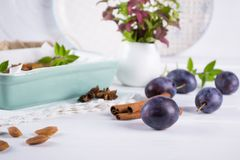 Group of fresh purple plums on a white kitchen table. Ready for cooking Stock Photos