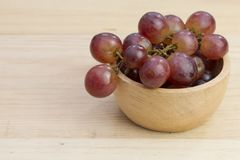 Group of fresh red grape in bowl on wood table Royalty Free Stock Photo