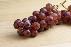 Group of fresh red grape on wood table.  Royalty Free Stock Photos