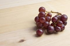 Group of fresh red grape on wood table.  Stock Image