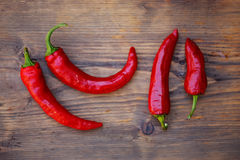 Group of fresh red hot chilli peppers on an old vintage wooden table Royalty Free Stock Images