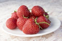 Group fresh red strawberries white plate on beige scarf, clean, delicious and ready to eat. Group fresh red strawberries on white plate on beige scarf, clean Royalty Free Stock Photos