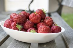 Group fresh red strawberries white plate, clean fruits, delicious and ready to eat. Group fresh red strawberries on white plate on wooden bench, ripened and Stock Photography