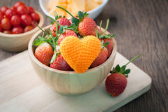 Group of fresh ripe strawberry on wood plate with orange heart s Stock Images