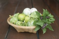 A group of fresh vegetables in a basket. Green eggplants, green lemon and sweet basils. Selective Focus Stock Image