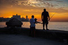 Group of friend fishing at Malecon,  in Havana, Cuba. Havana, Cuba - September 25, 2015: Group of friend fishing at sunset at Malecon,  most popular and famous Stock Photo