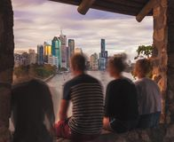 Group of friend on window against modern cityscape royalty free stock photography