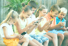 Group of friendly children playing with mobile phones outdoors Stock Photo