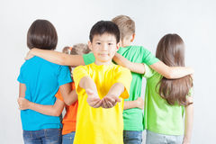 Group of friendly childrens like a team together. Asian boy holding your idea at his hands. Peaceful. Friendship. Kids. Conceptual image Stock Photography