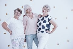Group of friendly senior women enjoying meeting against white wa. Ll with gold dots stock photography