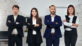 Group of friendly stylish young business people in suit posing with crossed hand at office