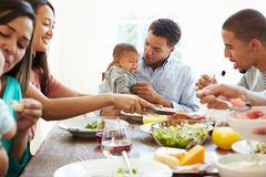 Group Of Friends With Babies Enjoying Meal At Home Together royalty free stock photos