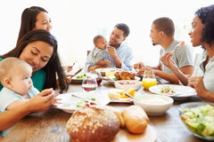 Group Of Friends With Babies Enjoying Meal At Home Together royalty free stock images