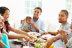 Group Of Friends With Babies Enjoying Meal At Home Together Stock Photo