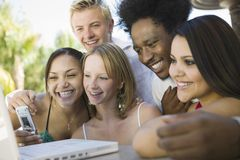 Group of friends at back yard table using laptop and cell phone close up Stock Photos