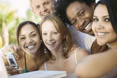 Group of friends at back yard table using laptop and cell phone portrait close up Stock Image