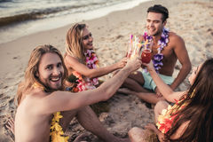 Group of friends on beach. Cheers! Group of young attractive friends are having fun on beach and drinking cocktails. Party in Hawaiian style stock photo