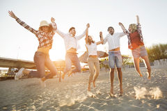 Group of friends on beach having fun. Group of friends together on beach jumping and having fun Royalty Free Stock Image