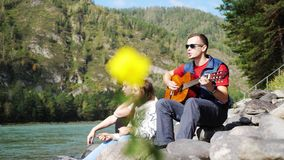 Group of cheerful friends on the beach playing guitar on a summer day next to mountain river. 3840x2160, 4k stock footage