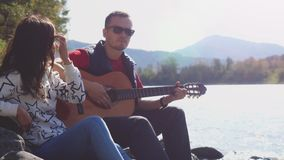 Young couple on the beach playing guitar singing song on a summer day next to mountain river. 3840x2160 stock footage