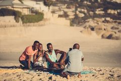 Group of friends on the beach taking pictures. Young men taking a photo of his friends on the seaside. Group of friends on the beach taking pictures Royalty Free Stock Photo