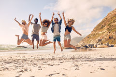 Group of friends on beach vacation. Portrait of group of friends going to on the beach. Mixed group of friends walking on the beach on summer day Stock Image