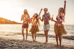 Group of friends on beach. Group of young attractive friends are having fun on beach, drinking cocktails, dancing and smiling. Party in Hawaiian style stock image