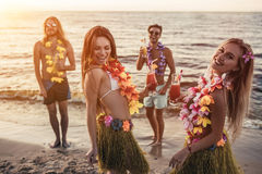 Group of friends on beach. Group of young attractive friends are having fun on beach, drinking cocktails, dancing and smiling. Party in Hawaiian style royalty free stock image