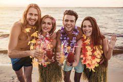 Group of friends on beach. Group of young attractive friends are having fun on beach, drinking cocktails and smiling. Party in Hawaiian style Royalty Free Stock Photos
