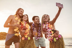 Group of friends on beach. Group of young attractive friends are having fun on beach, smiling and making selfie. Party in Hawaiian style stock photography