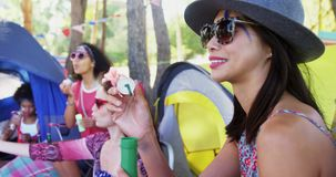 Group of friends blowing bubbles at music festival 4k. Group of happy friends blowing bubbles at music festival in park 4k stock footage