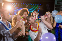 Group of friends blowing party horn in bar Royalty Free Stock Photography