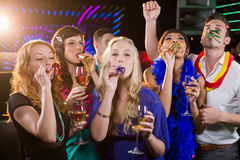 Group of friends blowing party horn in bar Stock Images