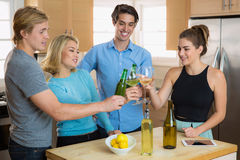 Group of friends buddies toasting beers and having a house party celebration for fun together Stock Photos