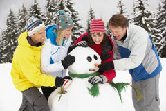 Group Of Friends Building Snowman On Ski Holiday Royalty Free Stock Photos