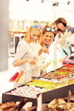 Group of friends buying jelly sweets on market Royalty Free Stock Images