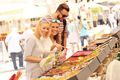Group of friends buying jelly sweets on market Royalty Free Stock Photography
