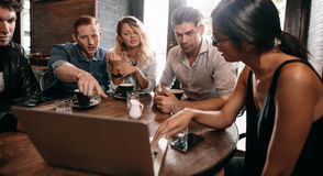 Group of friends at the cafe and looking at laptop Royalty Free Stock Photos
