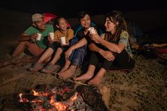Group of friends camping, sitting around camp fire. And drink coffee royalty free stock image