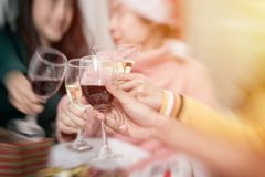 Group of friends celebrating Christmas at home and caps toasting stock photos