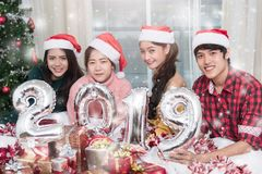 Group of friends celebrating Christmas at home and showing 2019 royalty free stock photos