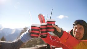 A group of friends celebrating a great winter day after skiing at the ski resort. Smiling friends spending time together and drink after skiing in cafe at ski stock footage